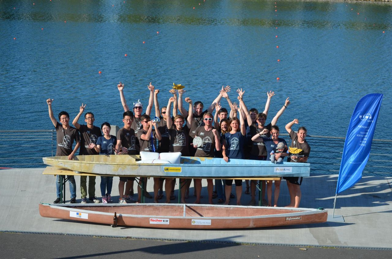 Group picture of the concrete canoe team in front of a river with a canoe