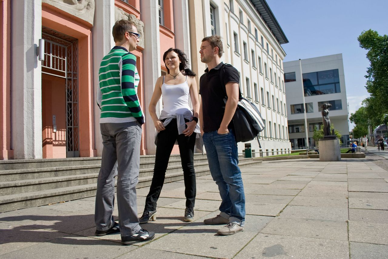 Three students chat in front of the Lipsius building