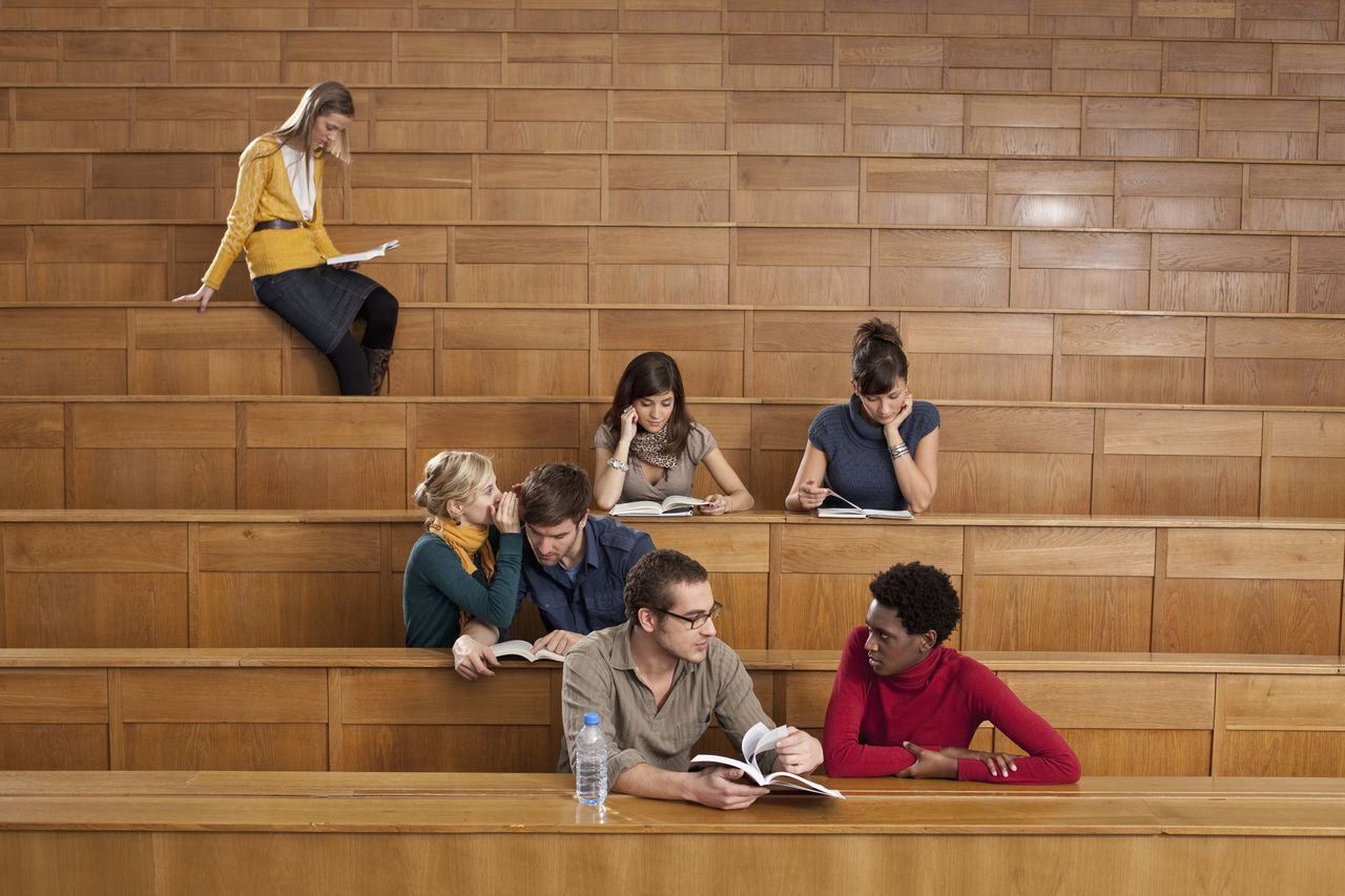 A few students sit in a lecture hall and talk to each other