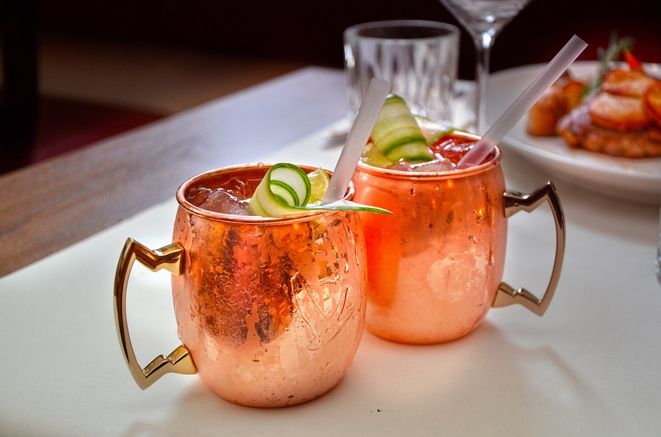 Two cocktails in bronze cups with ice and cucumber